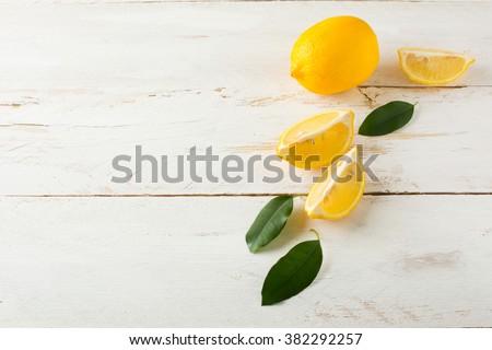 Juicy lemons with leaves on a white wooden background. Lemon slices. Lemon. Lemons. Citrus. Fruit. Fruits. Fresh Lemon. Juicy Lemons. Fresh Citrus. Fresh Fruit. Juicy Fruits.