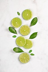 Juicy lime slices flat lay with green leaves on marble background. Top view