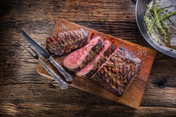 Juicy medium beef Rib Eye steak slices on wooden board with fork and knife herbs spices and salt.