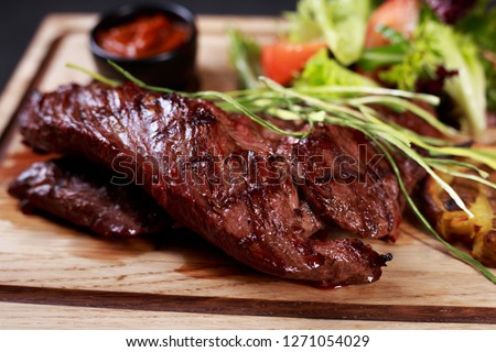 juicy medium rare skirt steak, hanging tender steak served with vegetable salad and potatoes on board, traditional american cuisine,grill and barbeque, meat restaurant menu