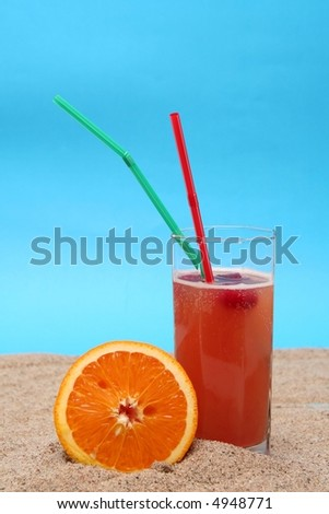Juicy orange on sand on a blue background
