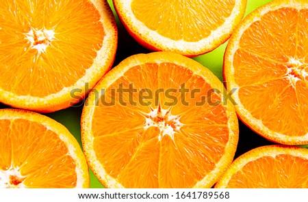Juicy oranges on a green background. The orange pulp. Orange background