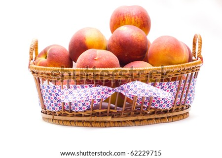 Juicy peaches in basket isolated