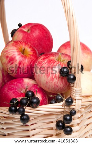 Juicy red apples  and blackcurrants in a basket, detail