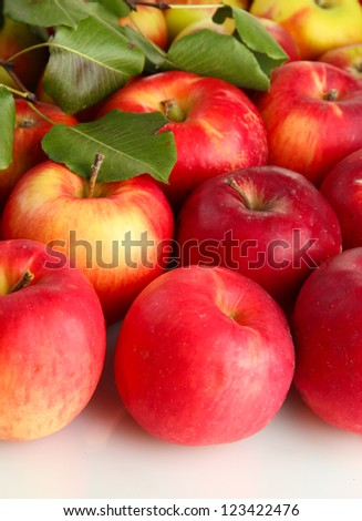 juicy red apples with green leaves, isolated on white