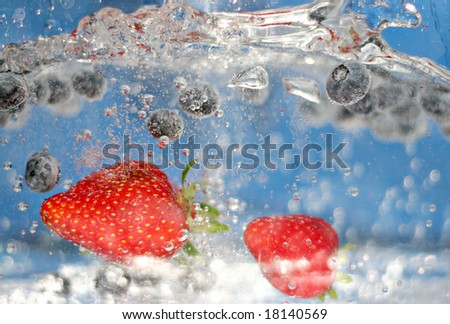 Juicy red strawberries and blueberries plunging into some sparkling water.  Shallow depth of field.