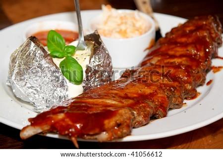 Juicy ribs with potato, tomato sauce and salad