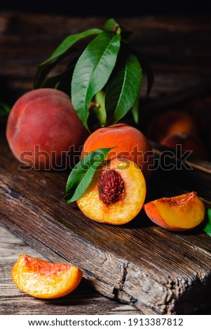 Juicy ripe peach on dark wooden rustic cutting board. Delicious farm peaches with leaves whole fruit in halves, peach with bone. Still life peach with in dark key. Vertical format.