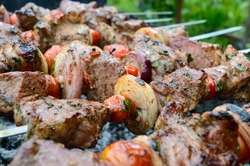 Juicy shish kebab from pork, tomatoes on skewers, fried on a fire outdoor on a background of nature. Barbecue. Close-up