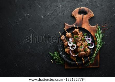 Juicy skewers of meat in a black plate. Barbecue, kebab. Top view. Free copy space.