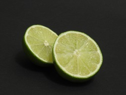 Juicy sliced pitted lime with a bright green peel on a dark background shot in close-up