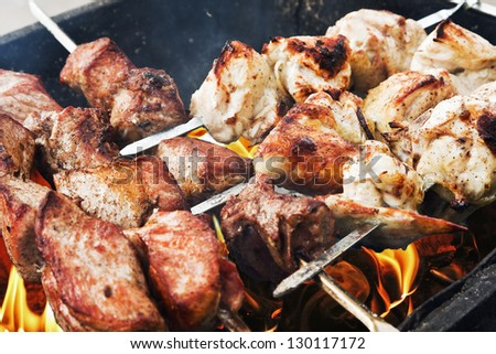 juicy slices of pork and chicken cooked over a fire. kebab.