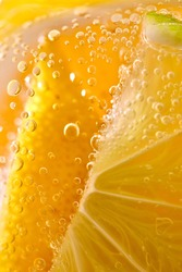 Juicy slices of ripe lemon with bubbles in a glass of water. Macro photo of refreshing lemonade