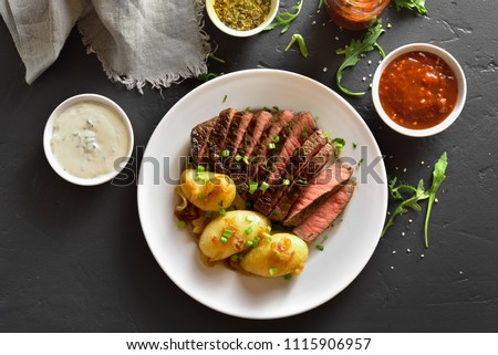 Juicy steak medium rare beef with baked potatoes on white plate over black stone table. Top view, flat lay