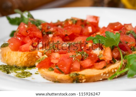 Juicy tomatoes on fresh bread, pesto as topping