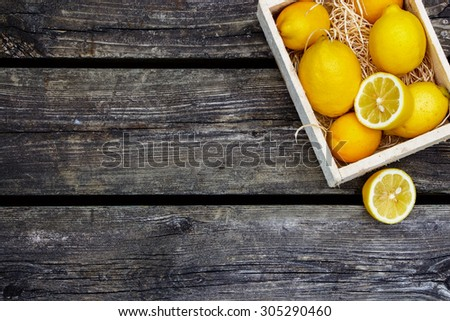 Juicy whole lemons and freshly cut half on rustic wooden background with space for text. Top view.