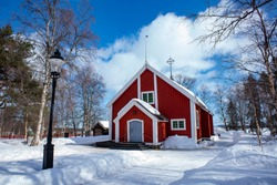 Jukkasjarvi Church, a Wooden red-colored church with a stand-alone bell tower in Swedish Lapland near Kiruna.