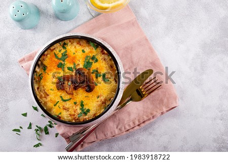 Julienne with potatoes and mushrooms in a baking dish on a light background, top view. Traditional French dish Stock photo ©