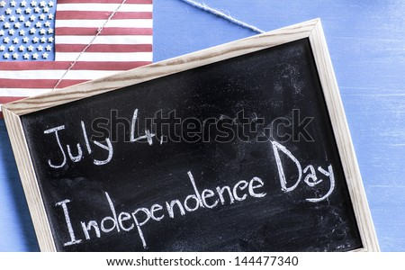 July 4, Independence Day Chalkboard and USA Flag made with edible stars and paper against blue wooden background.