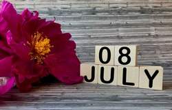 July 8. July 8 on wooden cubes on a wooden background..Peonies.Photos for the holiday
