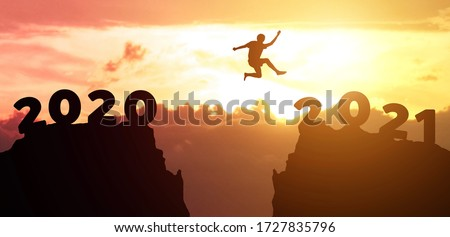Jump  from 2020 to 2021 new year concept, silhouette of man jumping over barrier cliff and success with beautiful sunset background. Happy New Year 2021 use for web banner and advertisement