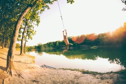 Jump into the water. A man is resting on the lake. A swing from a rope and a stick. Active recreation in nature. Summer fun. A man is riding a swing. Fisheye lens.