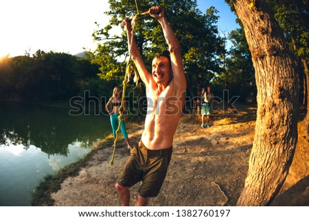 Jump into the water. A man is resting on the nature. A swing from a rope and a stick. Active recreation in nature. Friends have fun on the lake. Fisheye lens. #1382760197