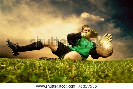 Jump of football goalman on the outdoor field