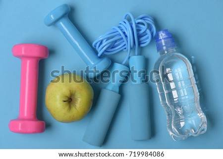 Jump rope, apple and barbells next to water bottle. Dumbbells and skipping rope in cyan and pink color on blue background, top view. Health regime and fitness symbols. Fit shape and sport concept #719984086
