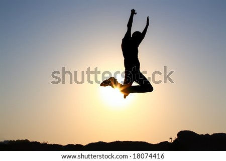 jump! silhouette of a young male jumping over sunset background - stock photo