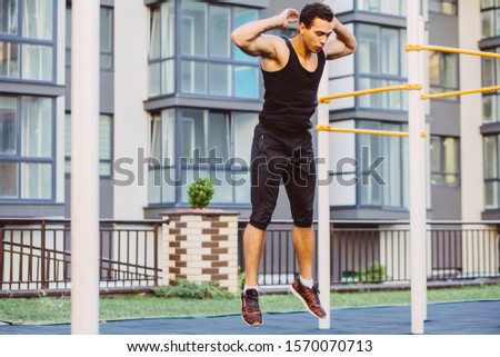 Jump up burpee. Sport exercises. Stage and release of squat. Exercises with free weight. Mixed race black man workout jump exercise on sport ground outdoor with urban cityscape on background.