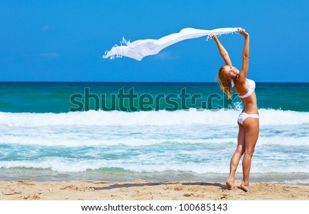 Jumping and dancing happy girl on the beach, fit sporty healthy sexy body in bikini, woman enjoys wind, freedom, vacation, summertime fun concept