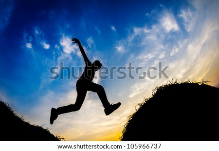 Jumping boy during sunset in Silhouette - stock photo
