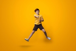 Jumping caucasian boy with red hair is wearing glasses and point at camera wearing a yellow shirt on a studio wall
