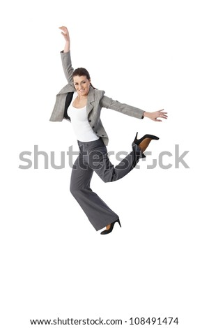 Jumping elegant woman smiling, posing in studio, smiling, arms wide open, leg in air, full length, cutout on white.