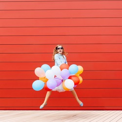 Jumping girl with colorful balloons in her hand. Outside. Red background. Outside