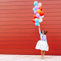 Jumping girl with colorful balloons in her hand. Warm sunny day. Outside. Red background