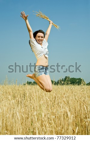 Jumping girl  with  wheat ear at  field in summer