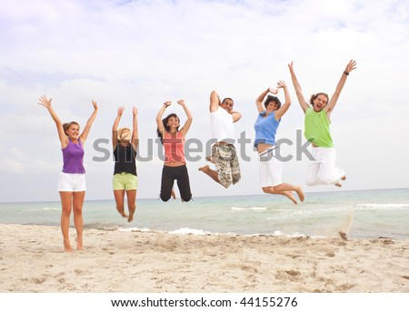 jumping group of happy people by the sea