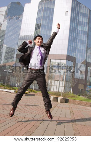 Jumping happy businessman over office buildings background