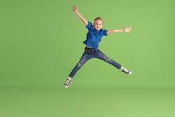 Jumping high. Happy boy playing and having fun on green studio background. Caucasian kid in bright cloth looks playful, laughting, smiling. Concept of education, childhood, emotions, facial expression