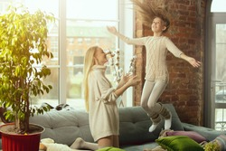 Jumping high. Happy loving family. Mother and daughter spending time together at home. Watching cinema, using laptop, laughting. Mother's day, celebration, weekend, holiday childhood concept.