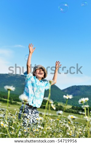 jumping little boy wants to catch soap bubbles