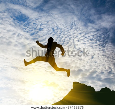 jumping man against blue sky.