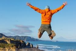 Jumping man on ocean coast, New Zealand