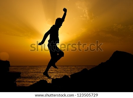 Jumping man silhouette in golden sunset hours with the sea background