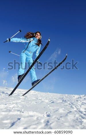 jumping pretty young woman in ski suit full of energy