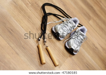 Jumping rope and trainers on a gym floor