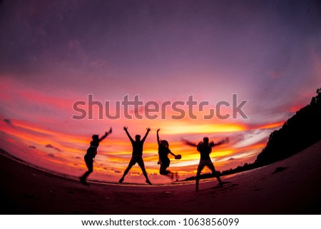 Jumping silhouettes sunset #1063856099