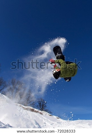 Jumping snowboarder against the blue sky